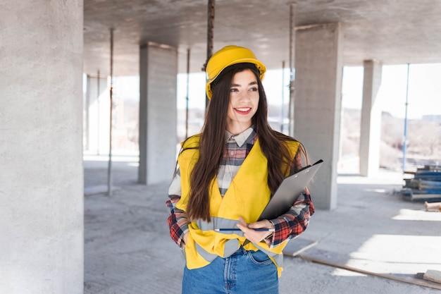 Trabalhador da construção civil feminino com uma prancheta na mão inspeciona o processo de construção