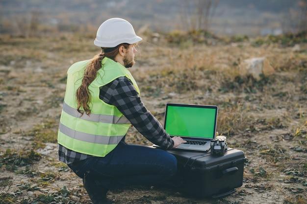 Trabalhador da construção civil, homem caucasiano, trabalhando com capacete de segurança e usando o laptop com display chave de croma