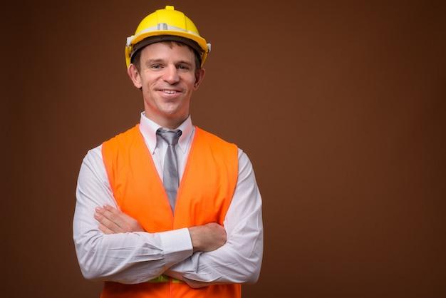 Trabalhador da construção civil homem contra parede marrom