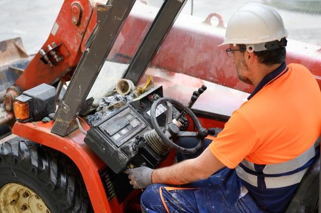 Trabalhador da construção civil iniciando a máquina escavadeira.