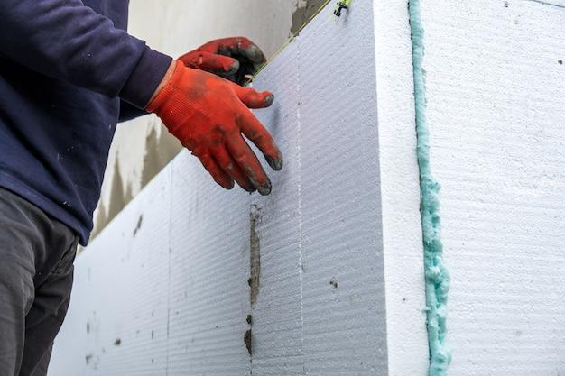 Trabalhador da construção civil instalando folhas de isolamento de isopor na parede da fachada da casa para proteção térmica.