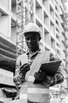 Trabalhador da construção civil jovem africano negro feliz, sorrindo enquanto segura a prancheta e usa o telefone celular no canteiro de obras