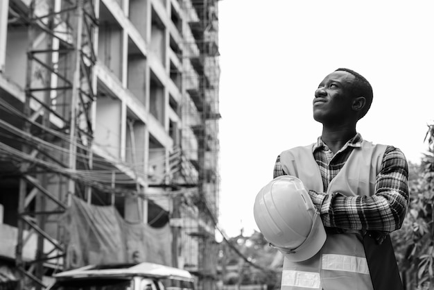 Trabalhador da construção civil jovem africano negro segurando a prancheta e o capacete com os braços cruzados no local de construção
