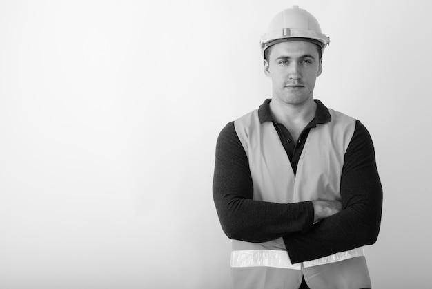 Trabalhador da construção civil jovem homem musculoso com os braços cruzados.