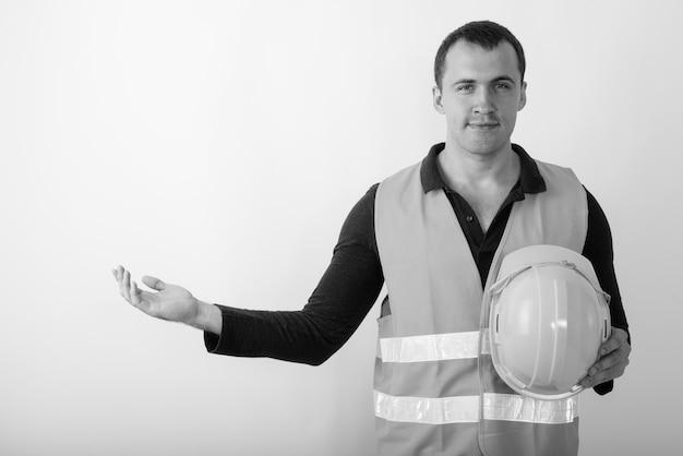 Trabalhador da construção civil jovem homem musculoso segurando capacete de segurança enquanto mostra algo