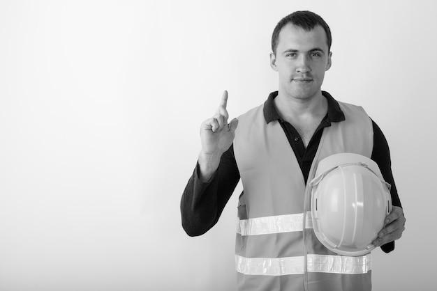 Trabalhador da construção civil jovem homem musculoso segurando o capacete enquanto aponta o dedo para cima.