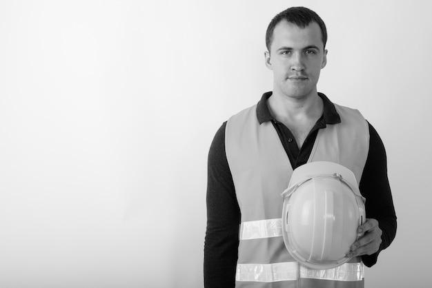 Trabalhador da construção civil jovem homem musculoso segurando o capacete.