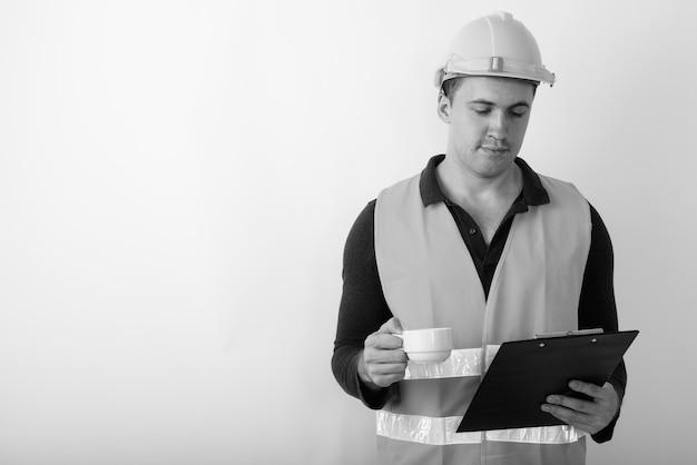 Trabalhador da construção civil jovem musculoso lendo na prancheta enquanto segura a xícara de café