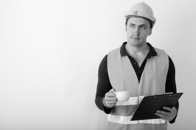 Trabalhador da construção civil jovem musculoso pensando enquanto segura a prancheta e a xícara de café