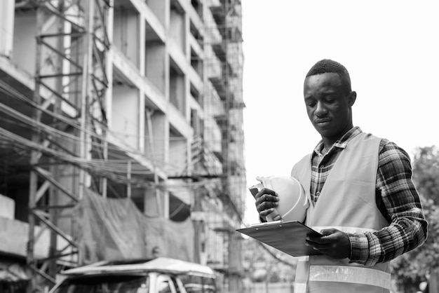 Trabalhador da construção civil jovem negro africano lendo na prancheta enquanto segura o capacete no canteiro de obras