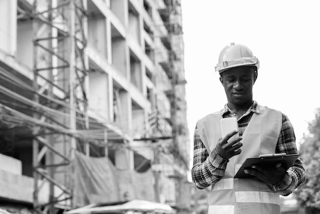 Trabalhador da construção civil jovem negro africano lendo na prancheta enquanto segura o celular no canteiro de obras