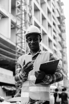 Trabalhador da construção civil jovem negro africano segurando a prancheta enquanto usa o celular no canteiro de obras