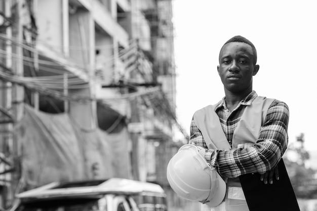 Trabalhador da construção civil jovem negro africano segurando uma prancheta e um capacete com os braços cruzados no local de construção