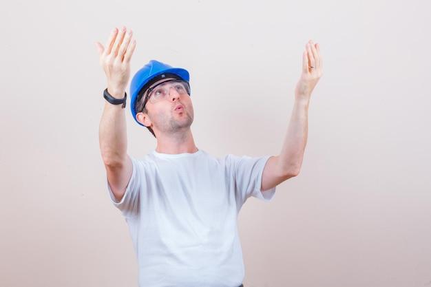 Trabalhador da construção civil levantando as mãos enquanto olha para cima em camiseta, capacete e parecendo surpreso
