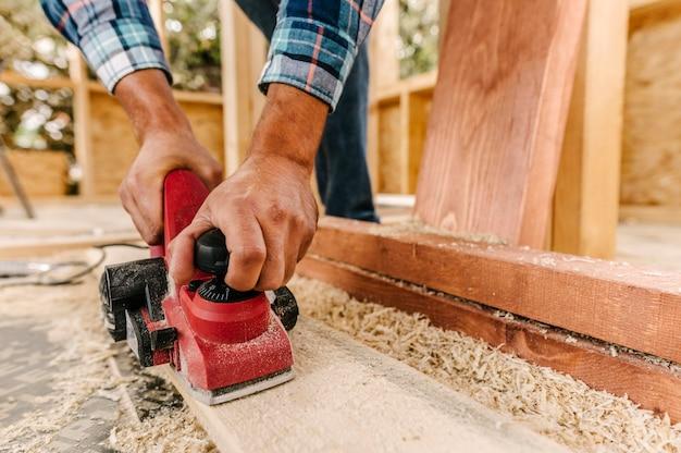 Trabalhador da construção civil lixando pedaço de madeira