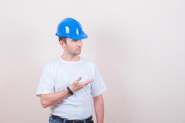 Trabalhador da construção civil mantendo a mão em um gesto perplexo em camiseta, jeans, capacete e olhando sério