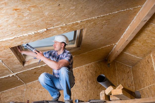 Trabalhador da construção civil masculino, construtor aplicando nova calafetagem à claraboia no teto de uma casa inacabada