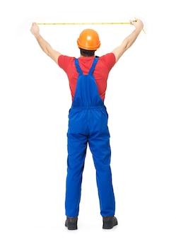 Trabalhador da construção civil medindo a parede em branco