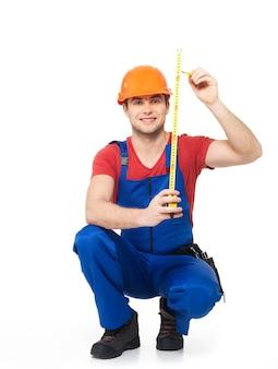 Trabalhador da construção civil medindo a parede sobre fundo branco - imagens do trabalhador manual.