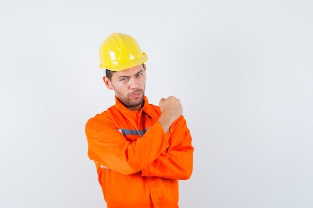 Trabalhador da construção civil mostrando o punho cerrado no uniforme, capacete e olhando confiante, vista frontal.