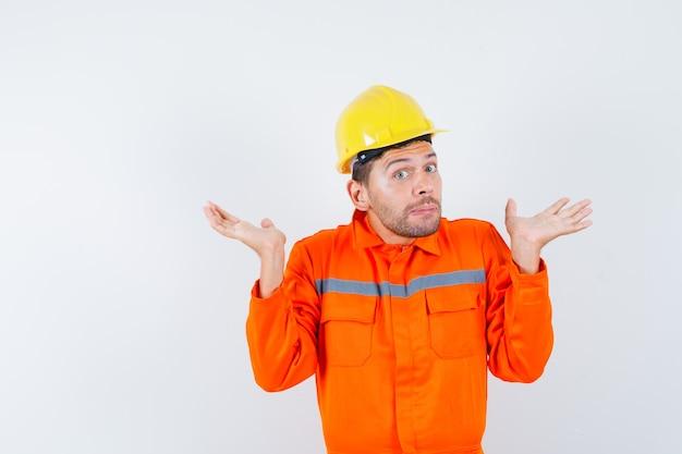 Trabalhador da construção civil mostrando um gesto desamparado no uniforme, capacete e parecendo confuso, vista frontal.