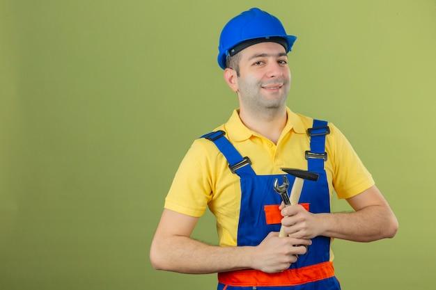 Trabalhador da construção civil no capacete de segurança uniforme e azul com sorriso no rosto em pé com martelo isolado no verde