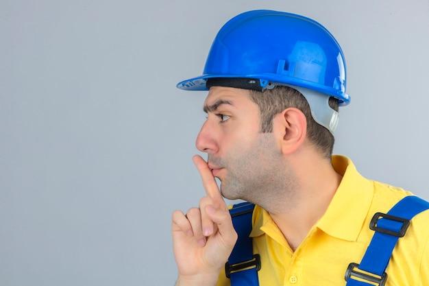 Trabalhador da construção civil no capacete de segurança uniforme e azul, fazendo o gesto de silêncio em branco isolado