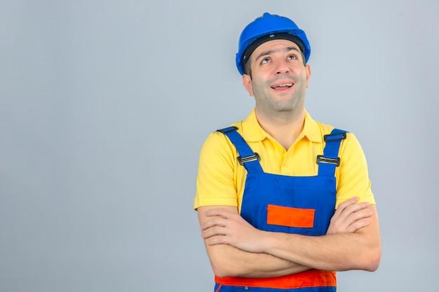 Trabalhador da construção civil no capacete de segurança uniforme e azul pensando com sorriso no rosto e cruzou as mãos em branco isolado