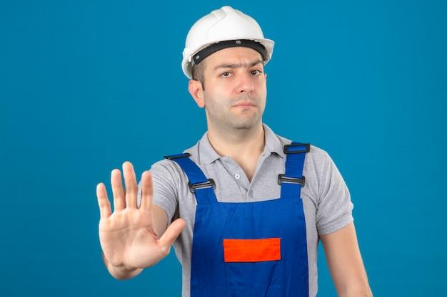 Trabalhador da construção civil no capacete de segurança uniforme e branco, fazendo o gesto de parada com a mão isolada no azul