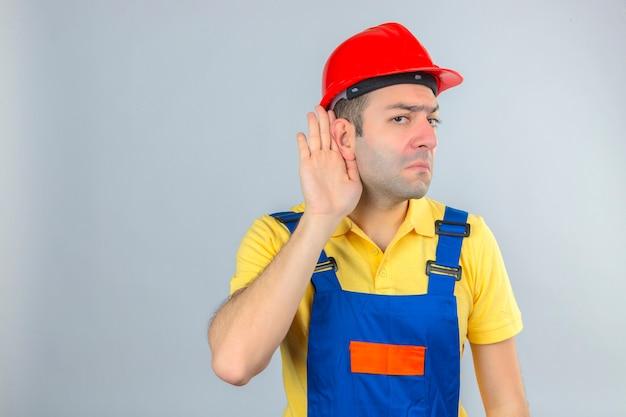 Trabalhador da construção civil no capacete de segurança uniforme e vermelho com a mão na orelha, ouvindo, isolado no branco