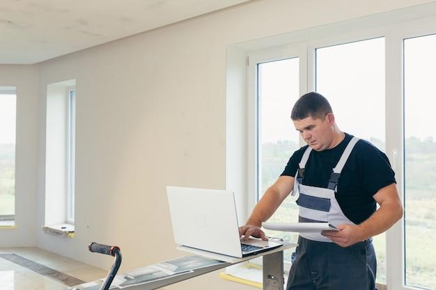 Trabalhador da construção civil olhando para laptop com projeto de construção