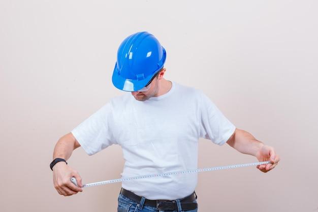 Trabalhador da construção civil olhando para medir a fita em t-shirt, jeans, capacete e olhando com cuidado