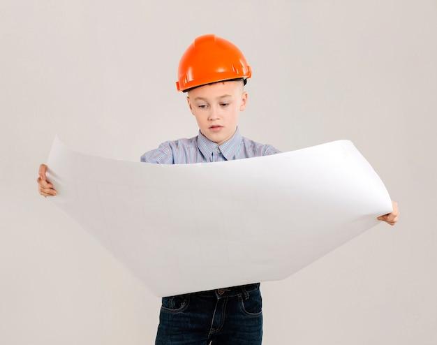Trabalhador da construção civil olhando para o projeto