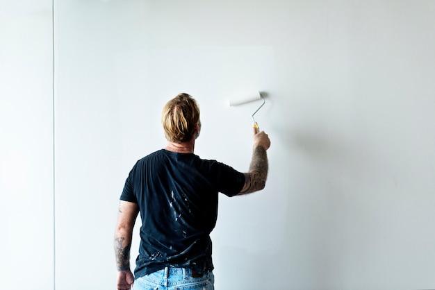 Trabalhador da construção civil pintando a parede