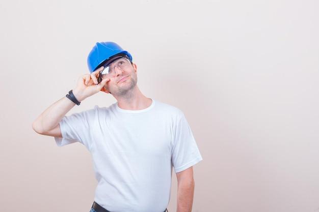 Trabalhador da construção civil posando olhando para cima de camiseta, capacete e parecendo esperançoso