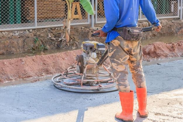 Trabalhador da construção civil produz a argamassa e acabamento concreto molhado com uma ferramenta especial