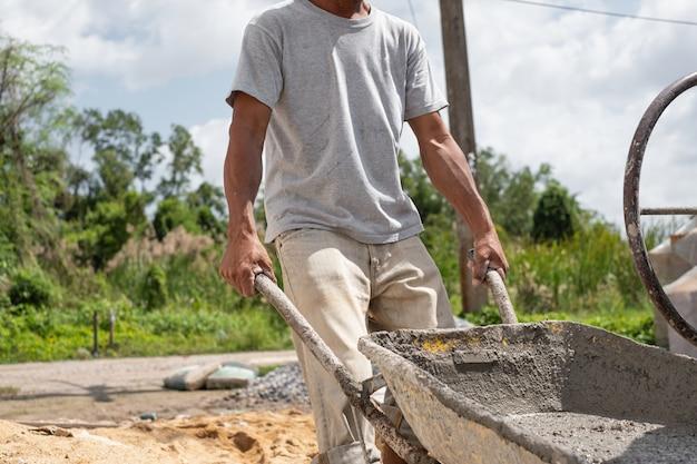 Trabalhador da construção civil puxar carrinho de mão. cimento pronto no carrinho de mão. equipamento da máquina de misturador de cimento no canteiro de obras.