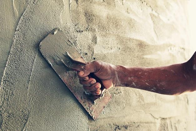 Trabalhador da construção civil reboco de cimento na parede