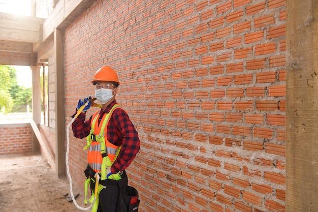 Trabalhador da construção civil roofer instala novo telhado, ferramentas de telhado, broca elétrica usada em novos telhados com folha de metal.