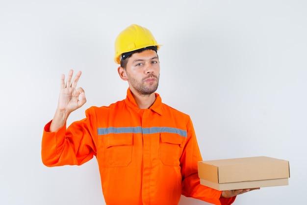 Trabalhador da construção civil segurando a caixa de papelão, mostrando o sinal de ok de uniforme, vista frontal do capacete.