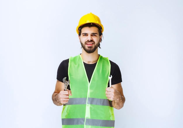 Trabalhador da construção civil segurando a chave inglesa para reparos mecânicos.