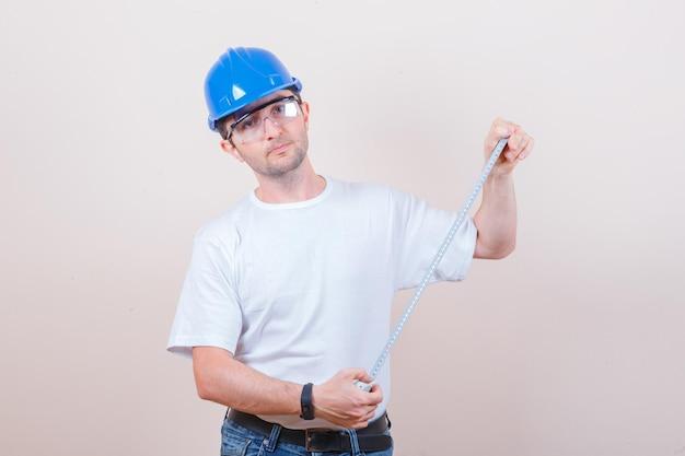 Trabalhador da construção civil segurando a fita métrica em uma camiseta, jeans, capacete e parecendo confiante