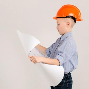 Trabalhador da construção civil segurando a vista lateral do projeto