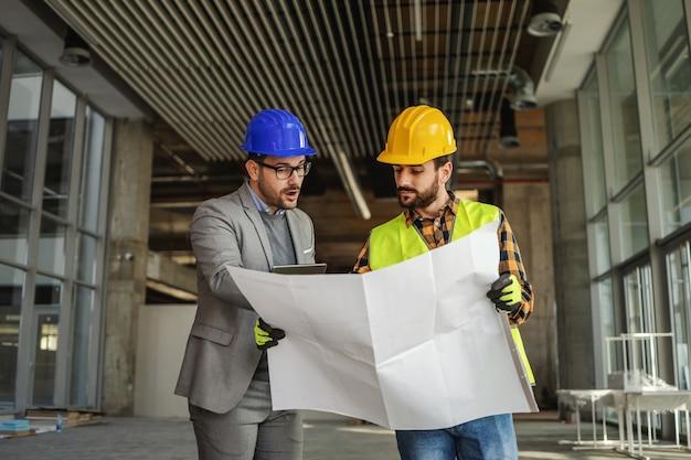 Trabalhador da construção civil segurando plantas e ouvindo sugestões do arquiteto falando sobre