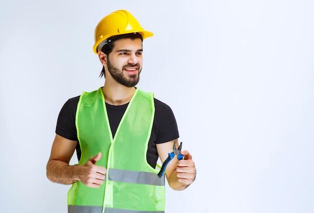 Trabalhador da construção civil segurando um alicate azul e aparecendo o polegar.