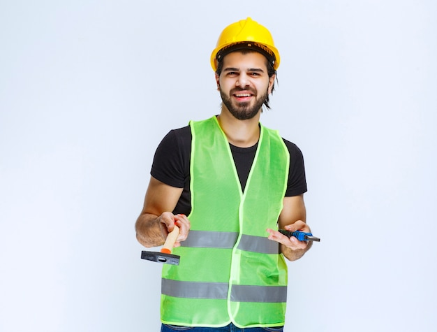 Trabalhador da construção civil segurando um alicate azul e o martelo de garra na mão.
