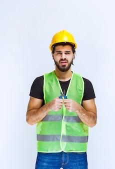 Trabalhador da construção civil segurando um alicate azul.