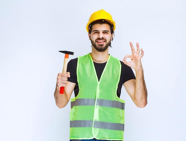 Trabalhador da construção civil segurando um martelo de garra e mostrando sinal de prazer.