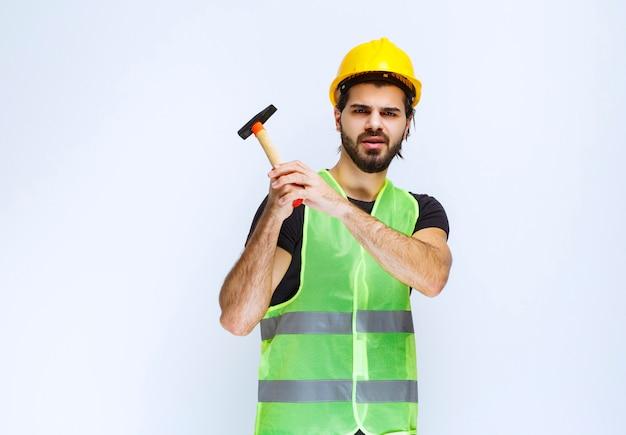 Trabalhador da construção civil segurando um martelo de garra.
