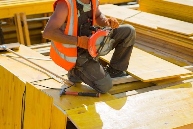 Trabalhador da construção civil segurando uma serra elétrica na madeira em um canteiro de obras